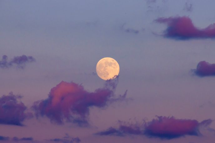 Full moon in a colorful sunset sky